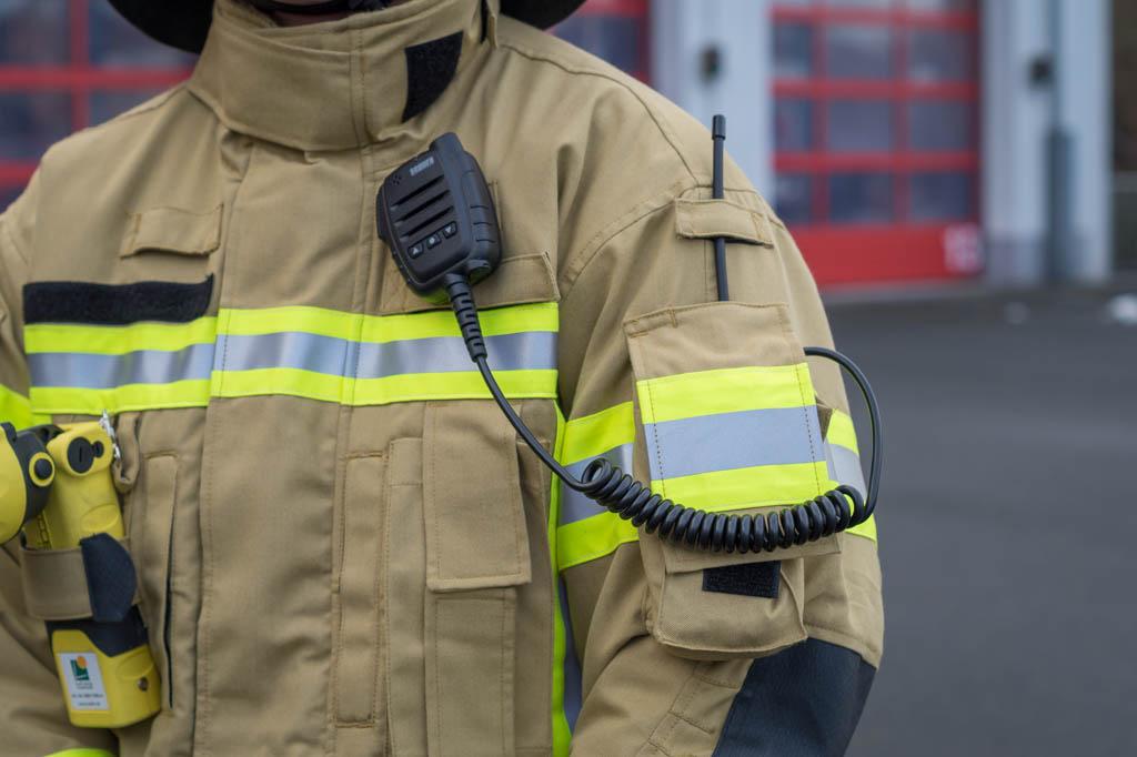 Das Funkgerät kann in aufgesetzten Taschen auf den Armen verstaut werden, für das Mikrofon ist eine Schlaufe unterhalb des Kragens vorgesehen.