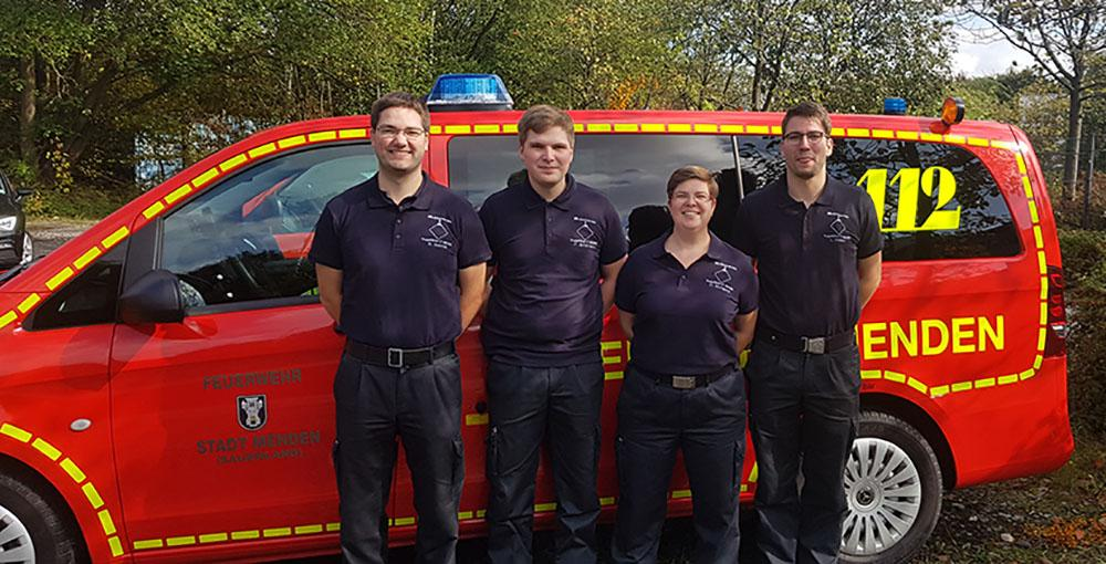 Simon Schmitt, Philipp Brinkmann, Christiana Bongard und Lukas Weber vor einem Feuerwehrfahrzeug