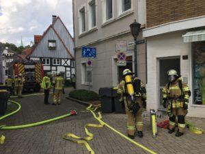 Feuerwehrleute stehen teils unter Atemschutz vor einem Haus